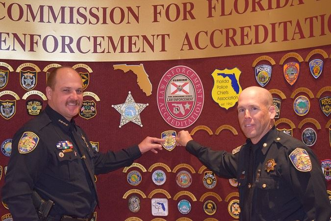 2 Police Officer adding their badge to the Commission for Florida Law Enforcement Accreditation boar